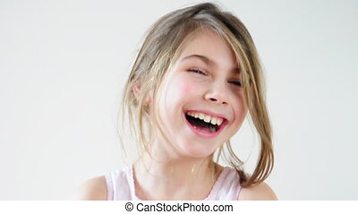 Close-up portrait of a happy little girl bursting in laugh