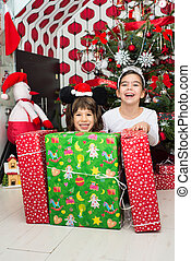 Laughing kids with Christmas gifts