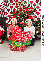Laughing kids with many Christmas gifts