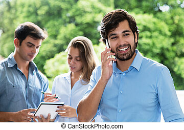 Laughing latin american businessman at phone with other...