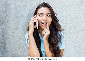 Laughing latin american woman at cellphone outdoors in...