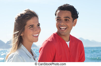 Laughing latin couple at beach