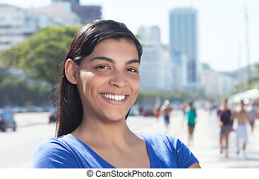 Laughing latin woman with long dark hair in the city
