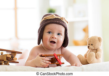 Laughing little baby weared pilot hat with airplane and teddy bear toys