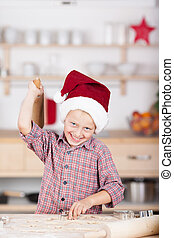 Laughing little boy baking Christmas cookies