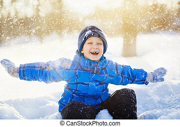 Laughing little boy, sitting in the snow park.