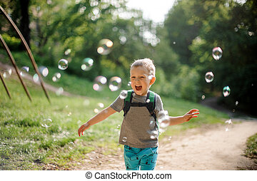 Laughing little boy with soap bubbles in summer park on sunny day
