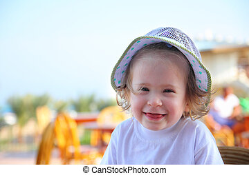 laughing little girl in hat