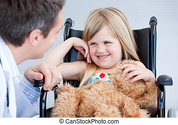 Laughing little girl sitting on the wheelchair at the hospital