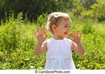 Laughing little girl standing in the grass