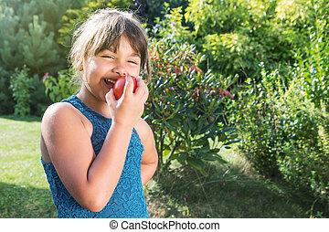 Laughing little girl tasting fresh tomato outdoors