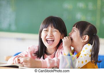 Laughing little girls sharing secrets in class