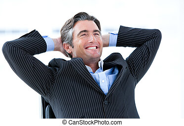 Laughing male executive thinking about his success in his...