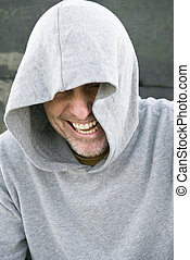 laughing man in hood. - A laughing man wearing a grey hooded...