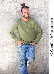 Laughing man standing with hands in pockets