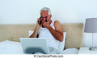 Laughing man using laptop while on