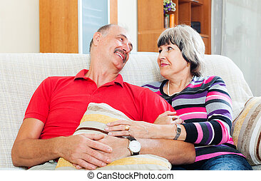 Laughing mature couple relaxing on couch