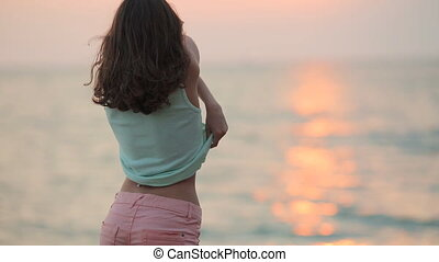 Laughing model removes t-shirt at sunset near the sea