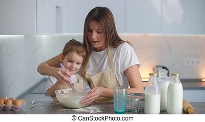 Laughing mom and daughter are cooking in the kitchen. The girl learns from her mother how to make a pie. Happy childhood