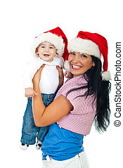 Laughing mother and baby boy with Santa hats