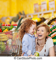 Laughing mother and daughter in a supermarket