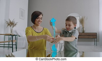 Laughing mother and son spend time together playing at home...