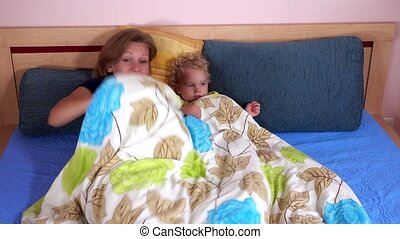Laughing mother with toddler girl playing in bed