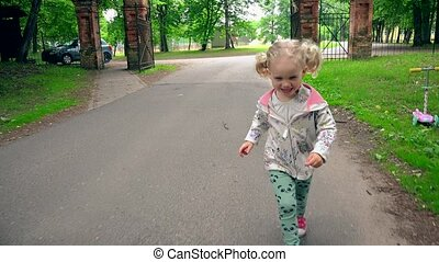 Laughing naughty girl running on park road. Cute toddler...