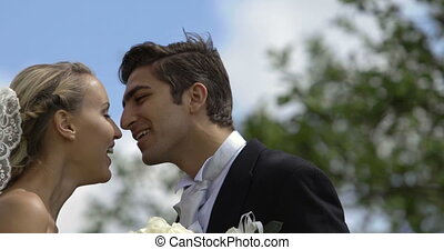 Laughing newlyweds kissing outside on a windy day on their...