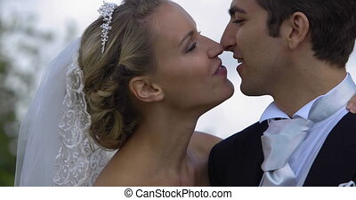 Laughing newlyweds kissing outside on their wedding day
