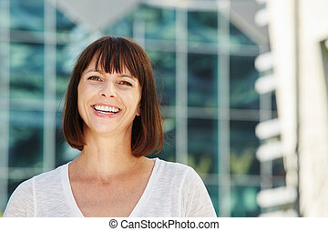 Laughing older woman standing outside in city