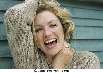 Laughing Outside - A blonde woman in her thirties holding up...