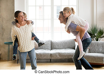 Laughing parents giving children piggyback ride playing together