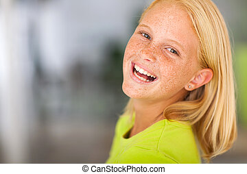 laughing preteen girl looking back headshot