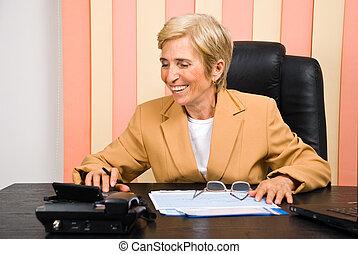 Laughing senior business woman using calculator