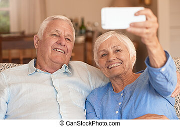 Laughing senior couple taking selfies with their cellphone...