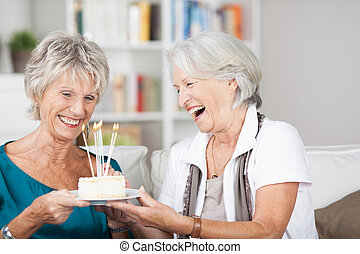 Laughing attractive senior ladies celebrate a birthday holding a plate with a small cake with burning candles as they laugh with enjoyment