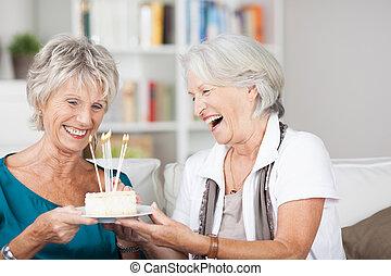Laughing senior ladies celebrate a birthday