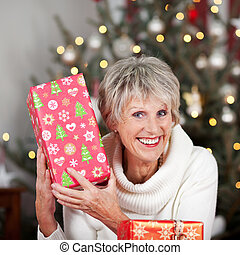 Laughing senior lady with a Christmas gift