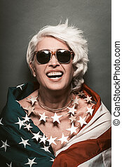 Laughing senior woman In sunglasses wearing American flag - ...