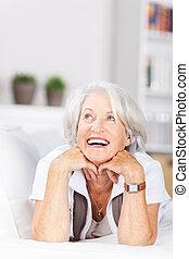 Laughing senior woman lying on a sofa
