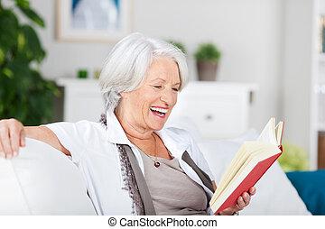 Laughing senior woman reading an amusing book