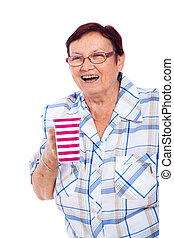 Laughing senior woman with mug