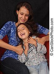 Laughing Sisters - A teenage Alaska Native girl tickles her...