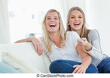 Laughing sisters sitting on the couch