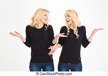 Laughing sisters twins looking at each other and shrugging shoulders