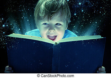 Laughing small boy with the old magic book