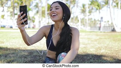 Laughing sportive girl chatting via phone in park -...