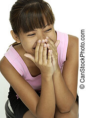 Laughing - A young pretty asian giil covers her mouth as she...