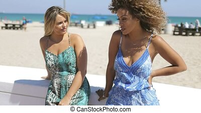 Laughing stylish women on tropical waterfront - Cheerful...